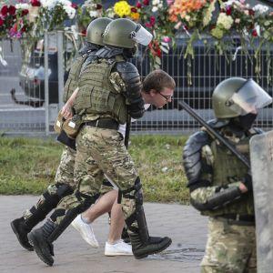 Maastopukuiset viranomaiset taluttavat mielenosoittajaa Minskissä Valko-Venäjällä.