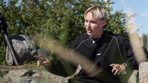 Isac Elliot sitter på ett berg.
