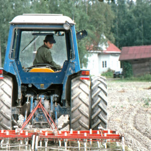 Taiteilija ja luomuviljelijä Osmo Rauhala peltotöissä traktorilla. Taustalla sukutilan rakennuksia.