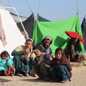 En familj sitter utanför ett tält.