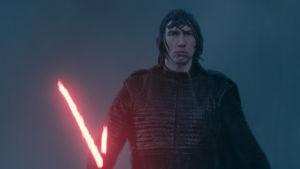 Närbild på Kylo Ren (Adam Driver) som går i ösregn och har ett draget lasersvärd.