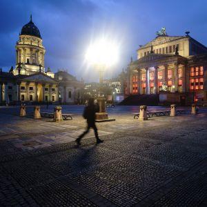 En ensam person går över torget Gendarmenmarkt.