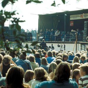 Yleisö kuuntelemassa esiintyjiä rock-konsertissa. Esiintymislava. Lavalla Jussi & The Boys -yhtye.