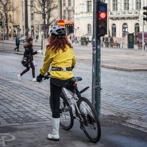 Polkupyöräilijä odottaa liikennevalon vaihtumista.