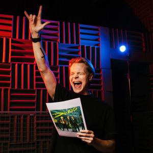 Olli Riipinen on nostanut kätensä äänitysstudiossa pystyyn Kaikki huutaa Dingo! -käsikirjoitus toisessa kädessään.