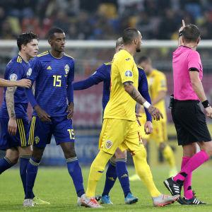 Svenska och rumänska fotbollsspelare följer efter domaren som pekar åt sidan.