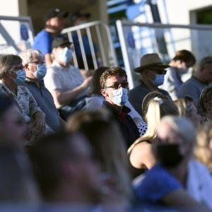 Katsojia urheilukilpailussa maskit kasvoillaan.