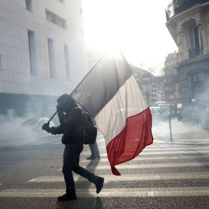 Ranskan lippua kantava mielenosoittaja taustalla savua.