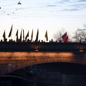 Uusnatsien Kohti vapautta! -marssi ylittämässä Pitkääsiltaa Kaisaniemestä Hakaniemeen natsien hakaristilippujen kanssa Helsingissä itsenäisyyspäivänä 6. joulukuuta 2018