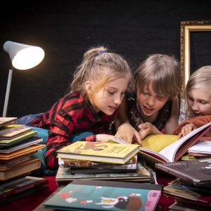 Tre barn läser böcker tillsammans.