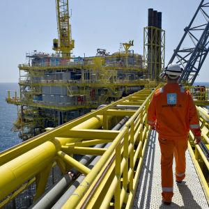 Työntekijä kävelee öljynporauslautalla.