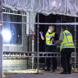 Kaksi poliisia tutkii ikkunaa johon on ammuttu