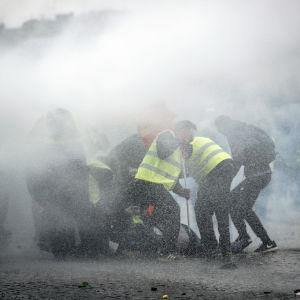 Gula västarna demonstrerar vid Triumfbågen i Paris. Polisen använder tårgas och vattenkanon.