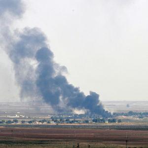 Den syriska gränsstaden Rads al-Ain brinner. På bilden syns staden på långt avstånd och svart rök som stiger upp från den.