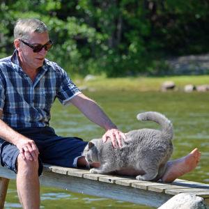 Peter Oljemark sitter på en brygga och klappar katten Oscar.