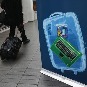 Flygpassagerare passerar en skylt om bagagegranskning på LaGuardia 26.1.2014