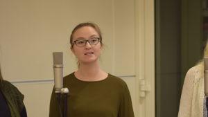 Emilia Ekström står vid en mikrofon och sjunger.