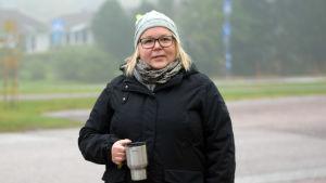En kvinna med svart rock och grå mössa och en termosmugg i handen står utomhus, en dimmig morgon. Sjundeå station/centrum. Hon håller också en tidning i sin andra hand.