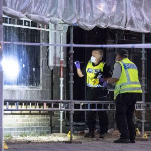 Två poliser undersöker skotthål i ett fönster. Framför fönstret står också byggställningar.
