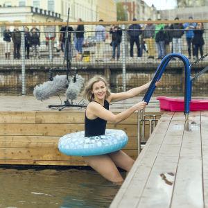 Märta Westerlund är iklädd baddräkt och en stor simring runt midjan. Hon klättrar ner för en stege, ner i en havssimbassäng utomhus.