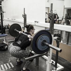 En kvinna och en man i ett gym. Kvinnan gör knäböj med en stång och vikter på axlarna som väger sammanlagt 80 kg. Mannen tittar på.