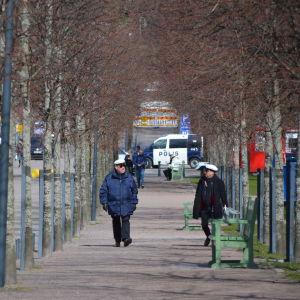 Första maj-firande i Brunnsparken i Helsingfors år 2020. Personer promenerar längs Stora allén.