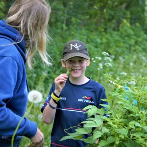 barn smakar på örter de har plockat i skogen