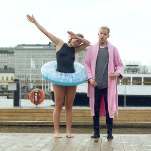 Märta Westerlund och Simon Karlsson står på kajen. Märta är iklädd baddräkt och Simon har vanliga kläder och en badrock. De är blöta eftersom de just doppat sig i havet.