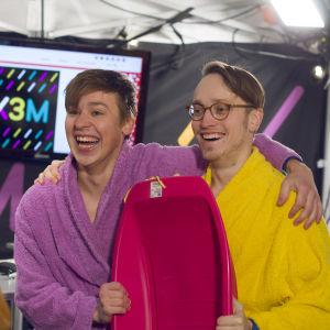 Jakob Norrgård och Axel Åhman iklädda badrockar. De håller i en rosa pulka och ska snart doppa sig i det kalla vattnet.
