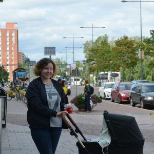 Kvinna står utomhus och framför sig har hon en barnvagn. Hon ler mot kameran och i sin vänstra hand håller hon en plastmugg med sugrör som innehåller en dryck.