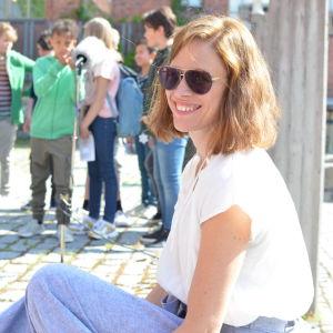 Redaktör Sandra Strömvall sitter leende med solglasögon på skolgård med skolbarn i bakgrunden.