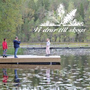 Människor på en brygga i skogsmiljö, en logo på bilden med orden vi drar till skogs.