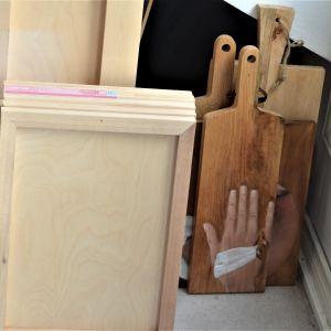baksidor av tavlor och några skärbräden i trä, på ett skärbräde är en hand med bandage runt målad