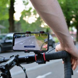 En smarttelefon på en cykelstång filmar cykelvägen framför cykeln.