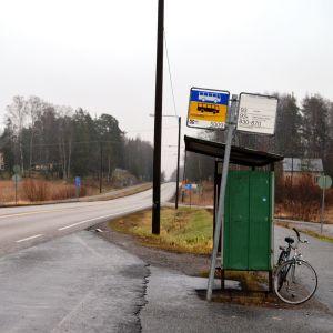 En busshålplats intill en landsväg sedd från sidan. Inga människor syns i bild, en cykel står parkerad bakom busskuren.