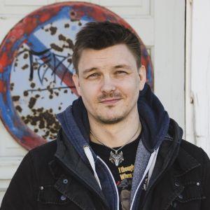 Zacharias Holmberg i munkjacka, t-skjorta och ett vargsmycke runt halsen står framför en vägg med ett gammalt trafikmärke.