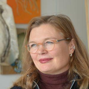 magdalena åberg, bakom henne syns några målningar oskarpt