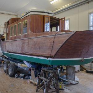 Fredrik Östman sköter om en träbåt i en verkstad.
