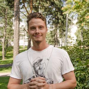 Joel Sjögren står bredvid en buske.