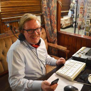 Programledare Ted Urho sitter i ett bås i Hagnäs hallen framför en dator.