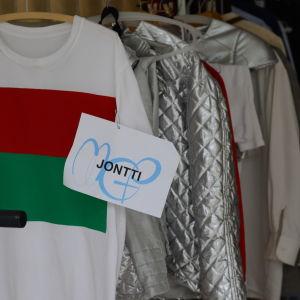 Kläder på en klädställning med en lapp med namnet Jontti skrivet.