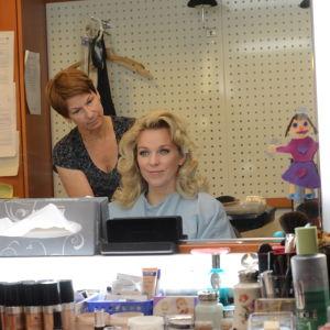 Anna-Karin Siegfrids sitter framför en spegel och får håret fixat.