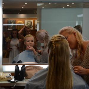 En flicka blir sminkad, via spegeln syns två andra barn.