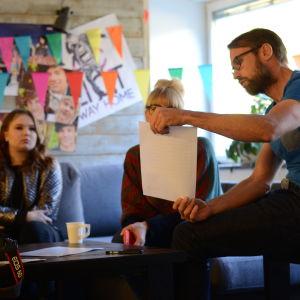 En man håller upp ett vitt papper för två kvinnor.