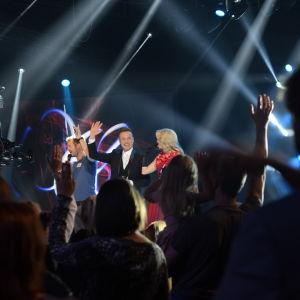 Tre människor på en scen och människor i förgrunden.