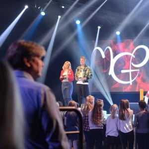 Anna-Karin Siegfrids och Jontti Granbacka är glada på en scen, människor i förgrunden.