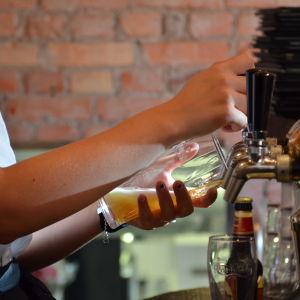 Barpersonal häller upp öl i ett glas från en ölkran.