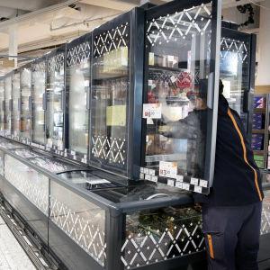 Myyjä täyttää kaupan kylmäkaappia.