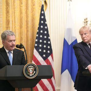 Sauli Niinistö till vänster och Donald Trump till höger talar vid varsitt podium. Trump tittar mot Niinistö medan Niinistö talar.