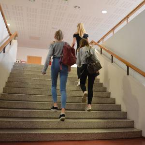 Tre flickor går upp för en trappa.